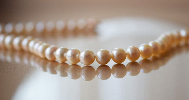 pearl necklace laying on reflective table