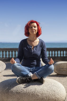 middle aged woman with medium red hair meditating on energy stones while looking at the camera
