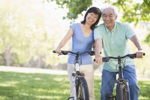 happy middle aged to older couple standing close to eachother while smiling and standing on bikes