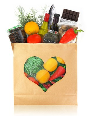 paper bag with a heart shaped cutout filled with foods for a healthy heart