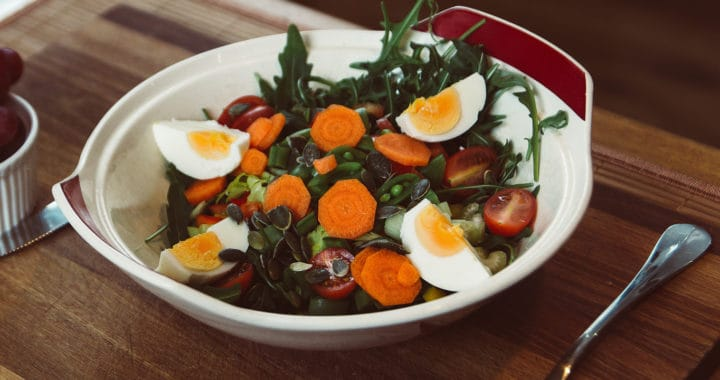 salad with carrots, tomatoes, peas, boiled eggs, and seeds