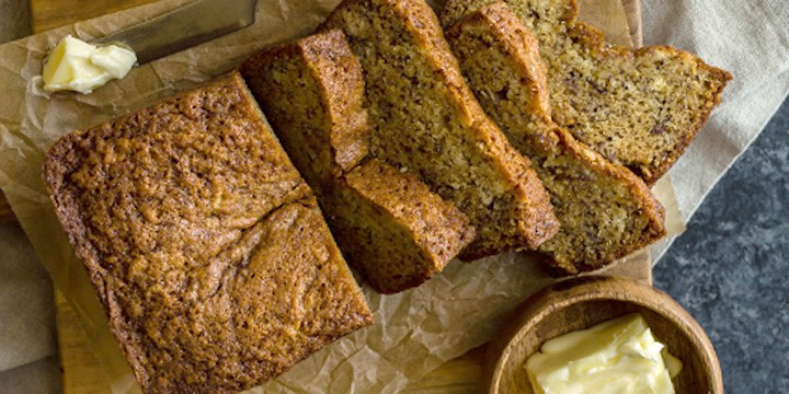 banana bread loaf with slices and a side of butter