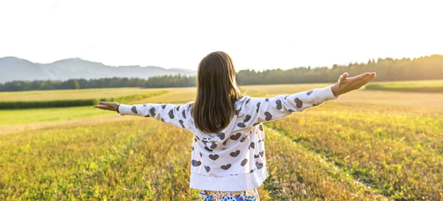 woman in white patterned jacket with arms open in sunny field