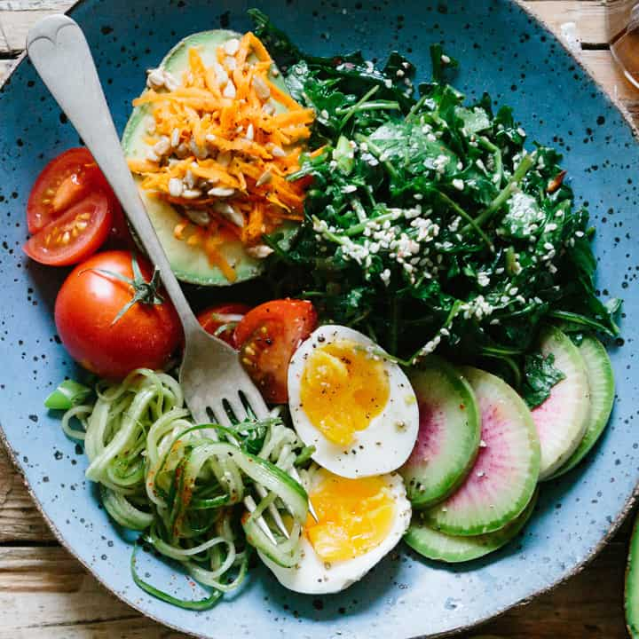 plate and fork with zucchini noodles, avocado with cheese, a hard boiled egg, tomatoes, steamed greens, and more