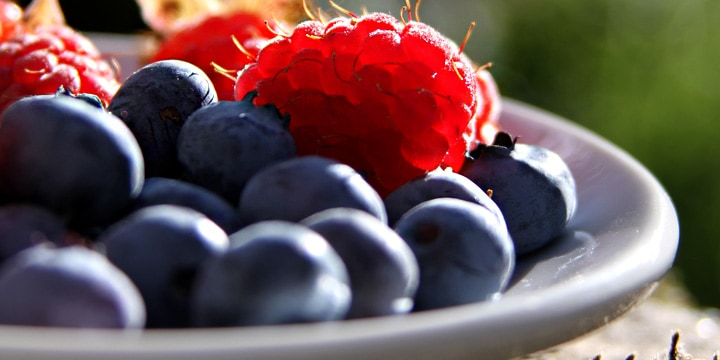 closeup of blueberries and raspberries in a bowl outside